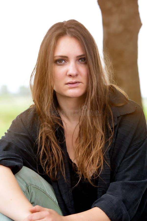 Piękna brunetki młoda kobieta siedzi outdoors obrazy stock