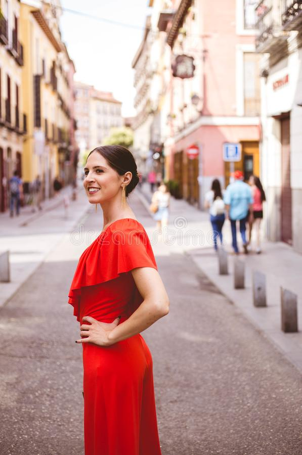 Piękna brunetki młoda kobieta uśmiecha się czerwonych niepokoje i jest ubranym z topknot ubiera odprowadzenie na ulicie bedsheet  obrazy stock