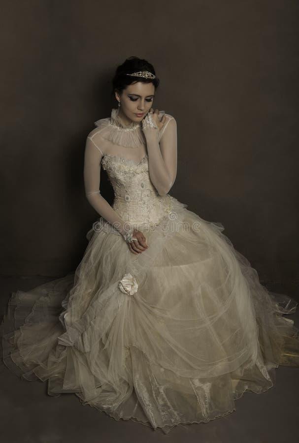 Piękna brunetki panna młoda jest ubranym rocznik ślubną togę zdjęcia stock