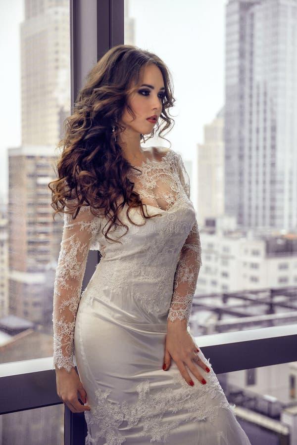 Piękna brunetki panna młoda pozuje blisko okno z miasta tłem zdjęcia royalty free