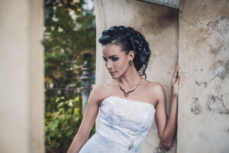 Piękna brunetki panna młoda w białej ślubnej sukni fotografia stock