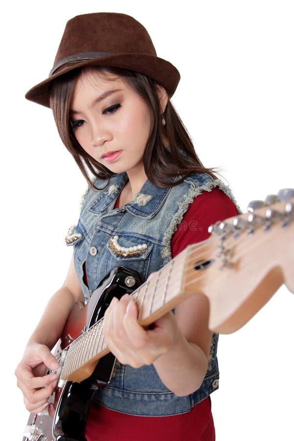 Piękna bujak dziewczyna bawić się jej gitarę elektryczną na bielu plecy, obraz royalty free