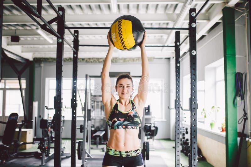 Piękna caucasian dziewczyna trzyma piłkę w gym Ubierający w wierzchołku i skrótach obraz royalty free