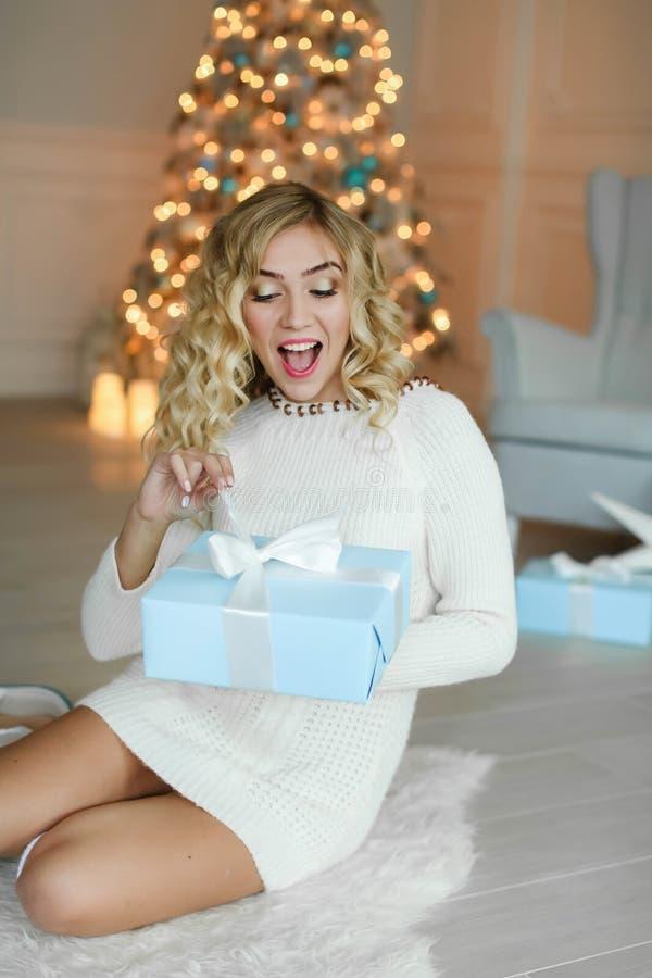 Piękna caucasian kobieta odwija prezenta pudełko Odświętność nowy rok i boże narodzenia, zima wakacje obraz stock