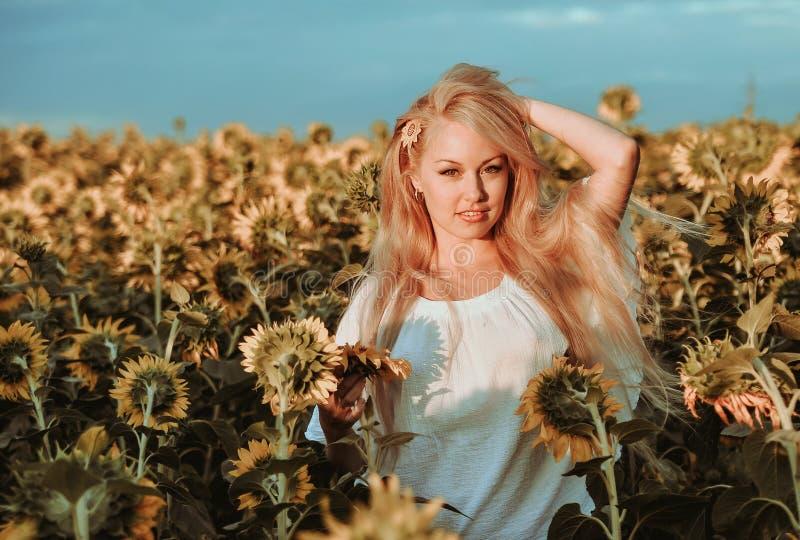 Piękna caucasian kobieta pozuje na łące z słonecznikami zdjęcia stock