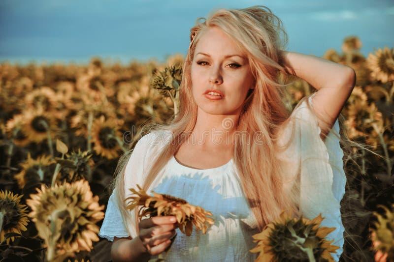 Piękna caucasian kobieta pozuje na łące z słonecznikami obraz stock