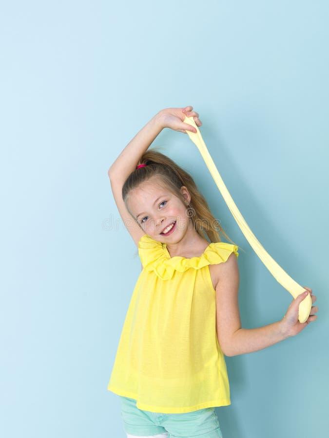 Piękna, chłodno i blondyny 9 roczniaka dziewczyna bawić się z kolorem żółtym szlamowym przed błękitnym tłem obraz royalty free