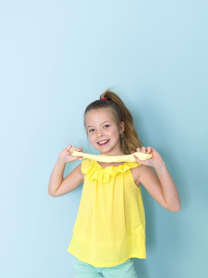 Piękna, chłodno i blondyny 9 roczniaka dziewczyna bawić się z kolorem żółtym szlamowym przed błękitnym tłem zdjęcie stock