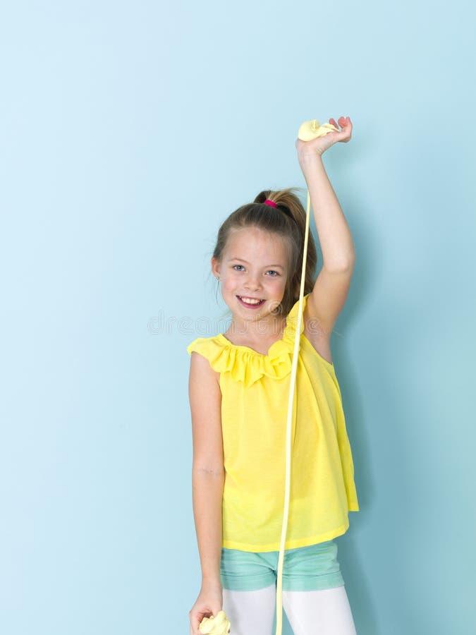 Piękna, chłodno i blondyny 9 roczniaka dziewczyna bawić się z kolorem żółtym szlamowym przed błękitnym tłem obrazy royalty free
