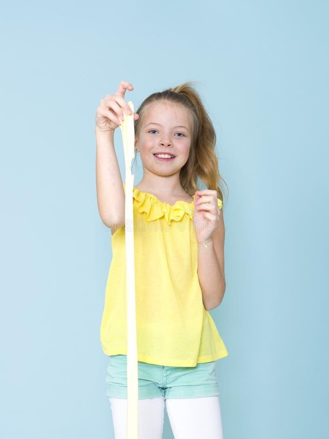 Piękna, chłodno i blondyny 9 roczniaka dziewczyna bawić się z kolorem żółtym szlamowym przed błękitnym tłem fotografia royalty free