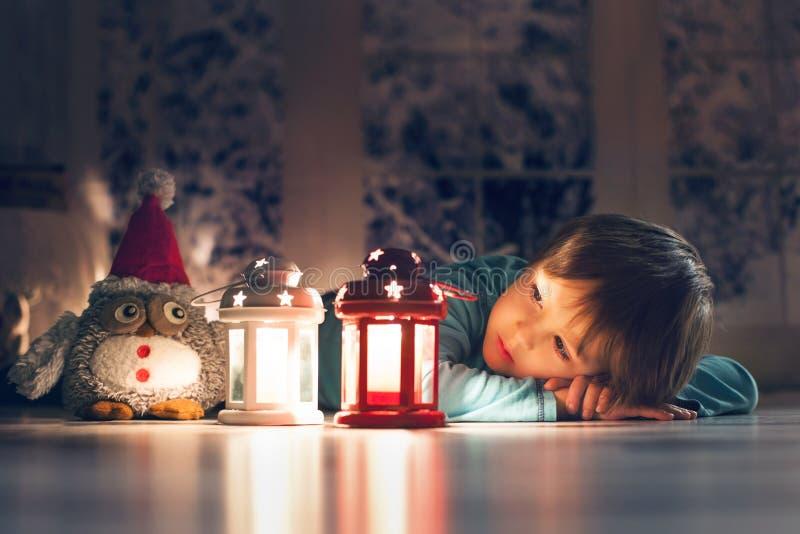 Piękna chłopiec, łgarski puszek na podłoga, patrzeje świeczkę obrazy stock