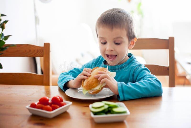 Piękna chłopiec, je kanapkę w domu, warzywa na fotografia stock