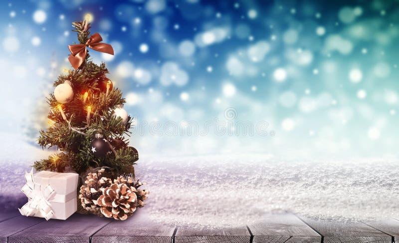 Piękna choinka dekoracyjna na stole z śniegiem na niewyraźnym kolorowym tle bokeh obraz stock