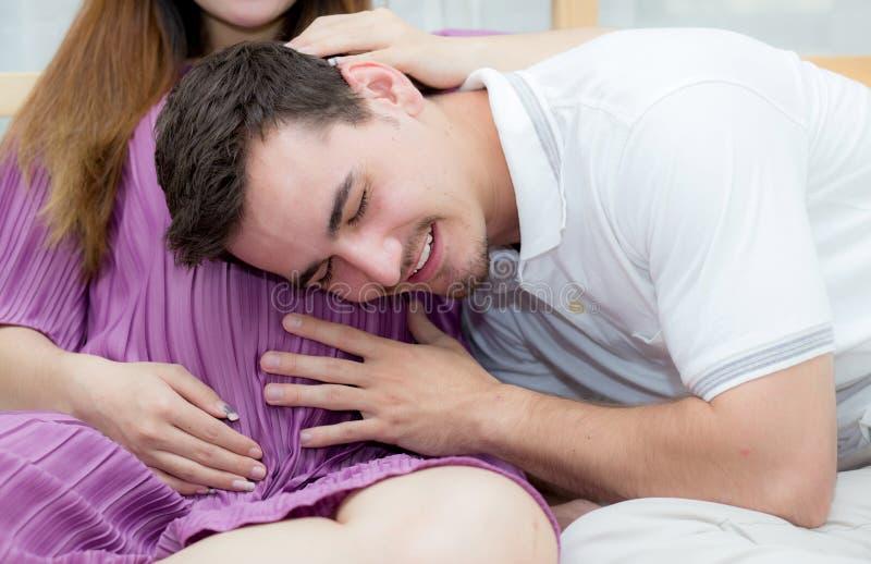 Piękna ciężarna azjatykcia kobieta i mąż słucha dziecko z brzuchem w sypialni zdjęcia stock