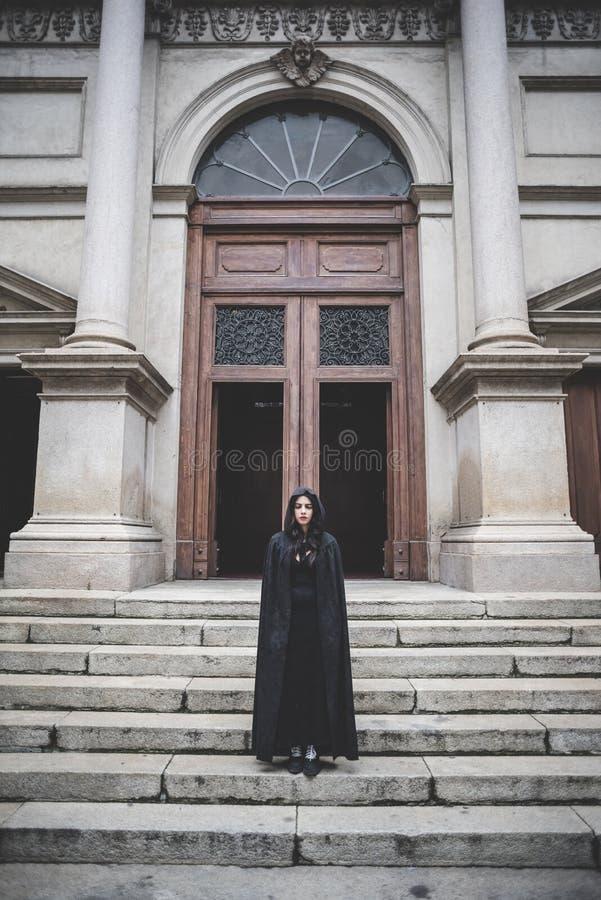 Piękna ciemna wampir kobieta z czarnym kapiszonem i salopą fotografia royalty free