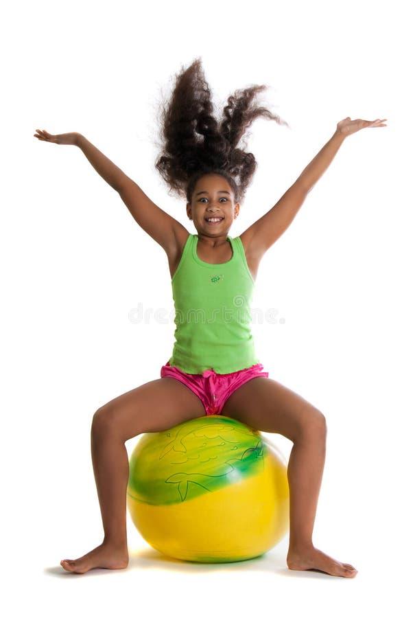 Piękna ciemnoskóra dziewczyna skacze na żółtej piłce dziewczyna podnosi up fotografia royalty free