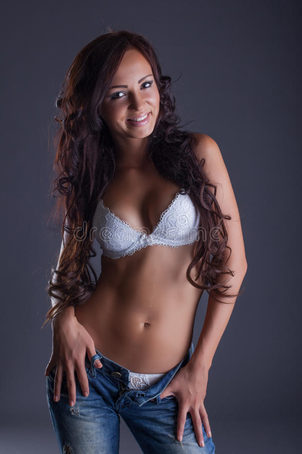Piękna curvy brunetka pozuje w staniku i cajgach zdjęcia stock