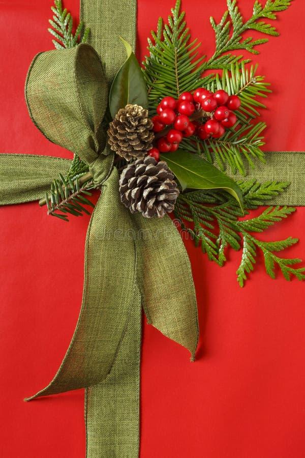 Piękna czerwień i zielony Bożenarodzeniowy prezent teraźniejsi z tkanina tasiemkowym łękiem i botanicznymi dekoracjami Pionowo tł obraz royalty free