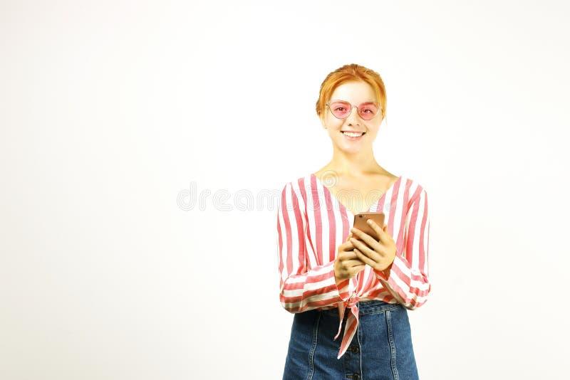 Piękna czerwień przewodził młodej kobiety pozuje, pokazuje emocjonalnych wyrazy twarzy i robi śmiesznym twarzom z telefonem komór obrazy stock