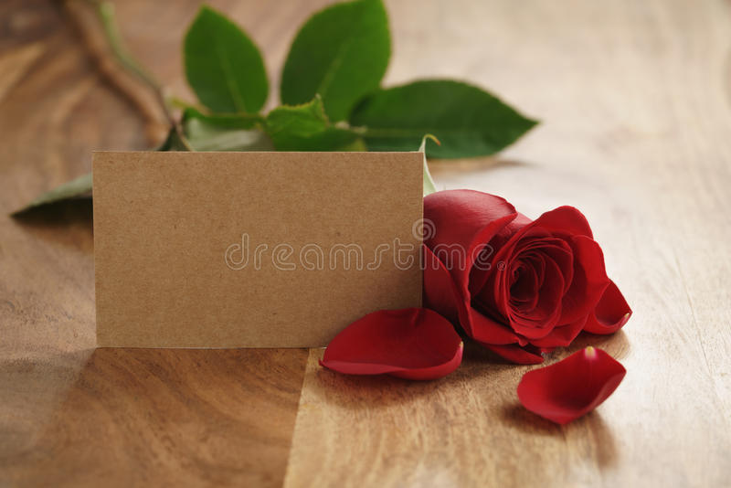 Piękna czerwieni róża z płatkami i pusta papierowa karta na starym drewno stole zdjęcie stock
