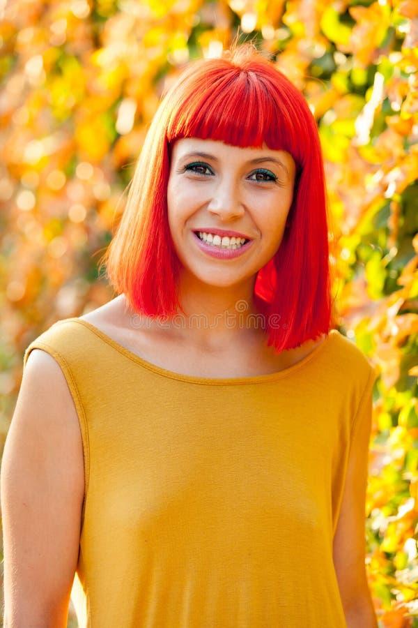 Piękna czerwona z włosami kobieta w parku zdjęcia royalty free