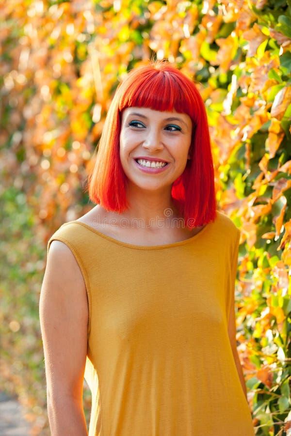 Piękna czerwona z włosami kobieta w parku zdjęcie stock
