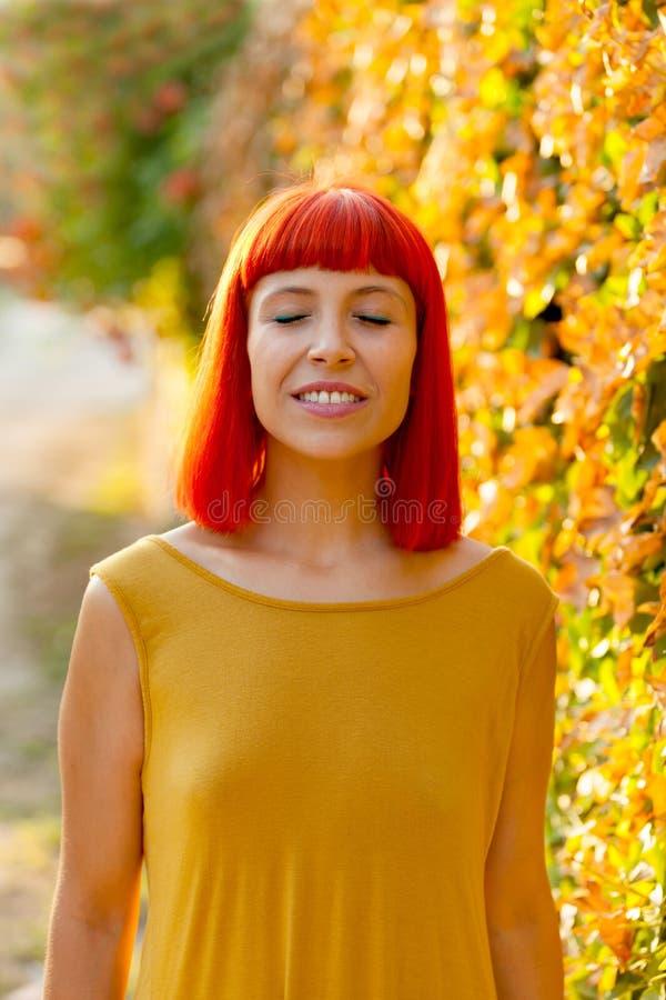Piękna czerwona z włosami kobieta z zamkniętymi oczami w parku zdjęcie stock