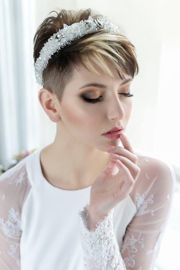 Piękna czuła elegancka młodej dziewczyny panna młoda w ślubnej sukni z koroną na głowie w studiu na białym tle z bukietem w rękac zdjęcie stock