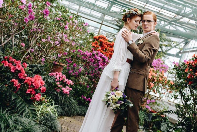 piękna czuła młoda ślub para z bukiet pozycją między kwiatami zdjęcie stock