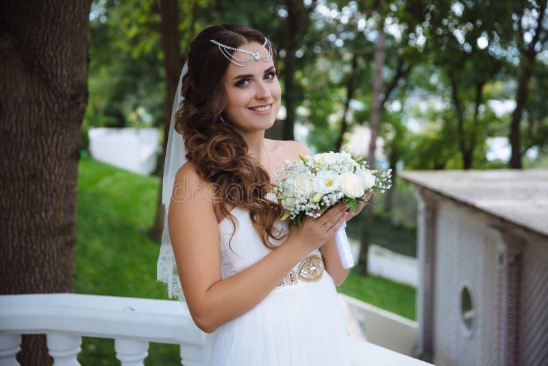 Piękna czuła panna młoda trzyma jej ślubnego bukiet i ono uśmiecha się szczęśliwie Ślubny wizerunek, poślubia stylowego pojęcie obraz stock