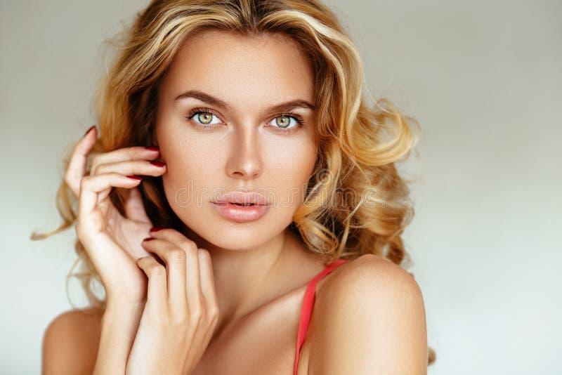 Piękna, czuła, seksowna blondynki dziewczyna z wargami bez makeup pozuje w różowej bieliźnie na białym tle, zdjęcia stock