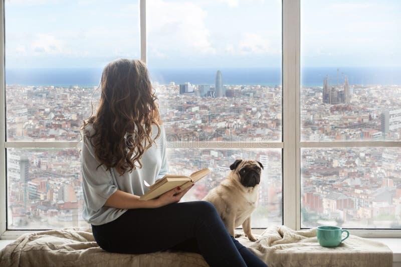Piękna długa z włosami kobieta z jej psim cieszy się Barcelona Hiszpania widokiem na zewnątrz okno zdjęcie stock