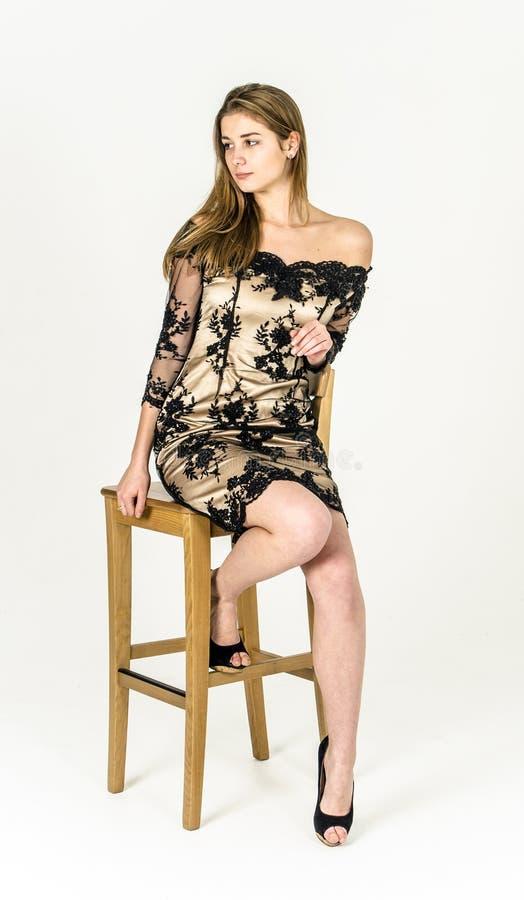 Piękna długowłosa młoda blondynki kobieta z nikłą postacią w czarnej mini sukni i złocie fotografia stock