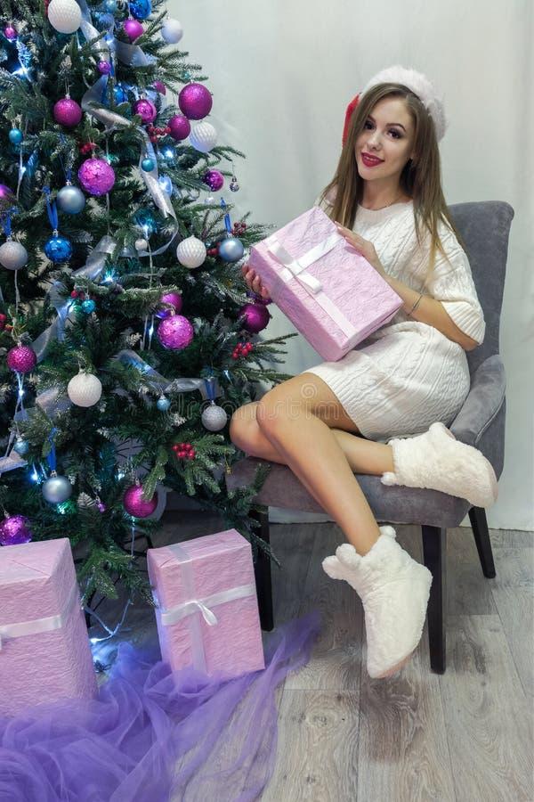 Piękna długowłosa uśmiechnięta dziewczyna w seksownym białym pulowerze siedzi na szarym krześle obok choinki Różowy prezenta pude zdjęcia royalty free