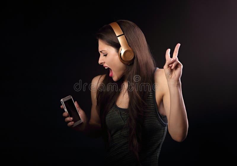 Piękna dancingowa młoda kobieta słucha muzycznego, pokazywać v sig obrazy stock