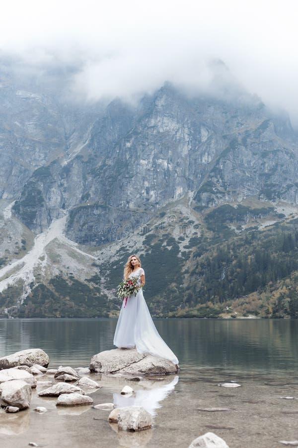 Piękna delikatna dziewczyna w lotniczej błękitnej panny młodej ślubnej sukni z luksusowymi kędziorami w górach blisko jeziora z ś zdjęcia stock
