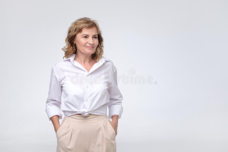 Piękna dojrzała biznesowej kobiety pozycja w biały nowożytny koszulowy patrzeć na boku zdjęcie royalty free