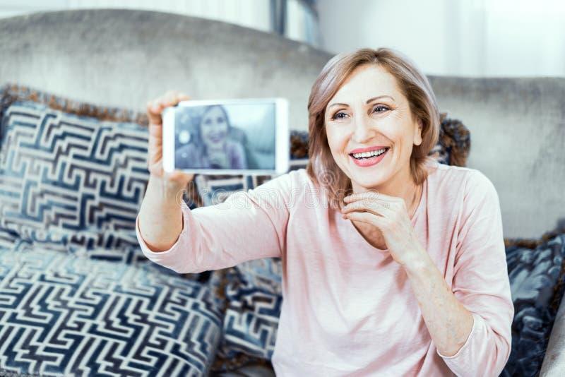 Piękna dojrzała kobieta bierze selfie w domu zdjęcie stock