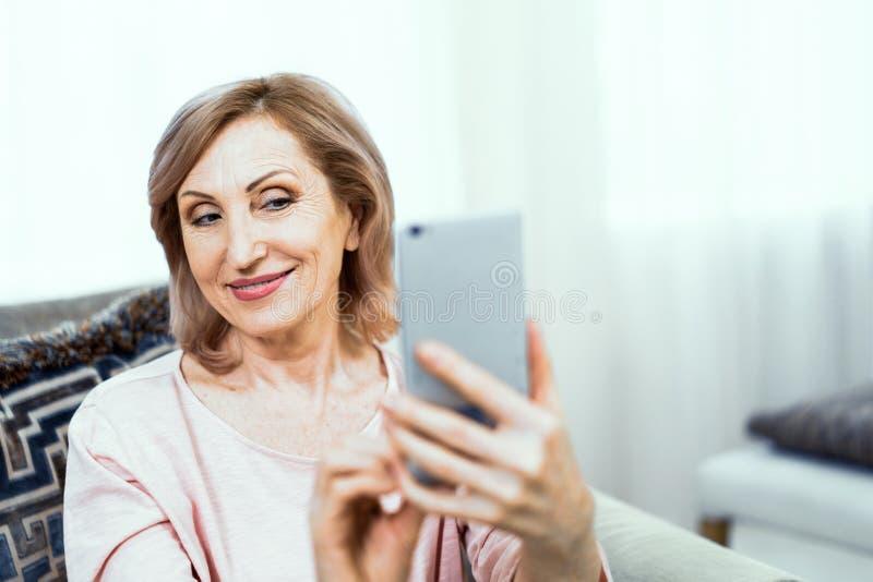 Piękna dojrzała kobieta bierze selfie w domu fotografia stock