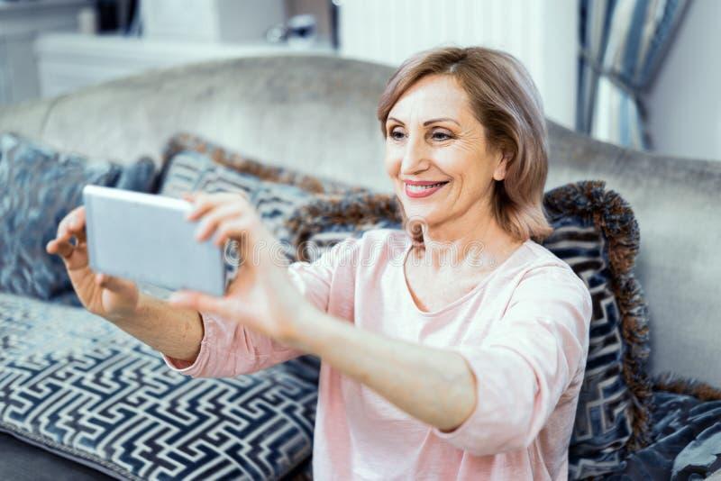 Piękna dojrzała kobieta bierze selfie w domu zdjęcia stock
