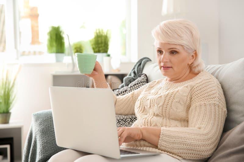 Piękna dojrzała kobieta pije kawę podczas gdy używać laptop w domu zdjęcie stock