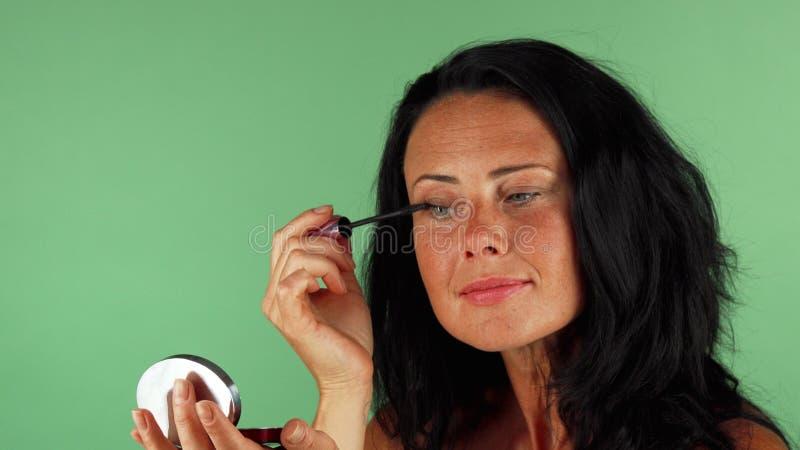 Piękna dojrzała kobieta stosuje makeup na zielonym chromakey obrazy stock