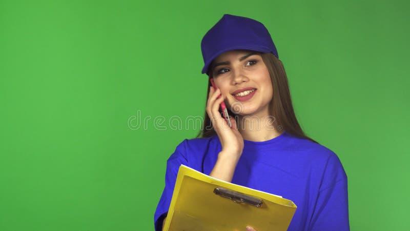 Piękna doręczeniowa kobieta opowiada na telefonie trzyma schowek zdjęcie stock