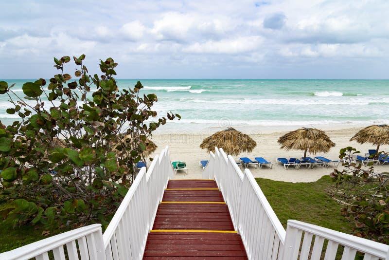 Piękna drewniana drabina ocean plaża Plaża z słomianymi parasolami i loungers Chmurny niebo i błękitne wody obraz stock