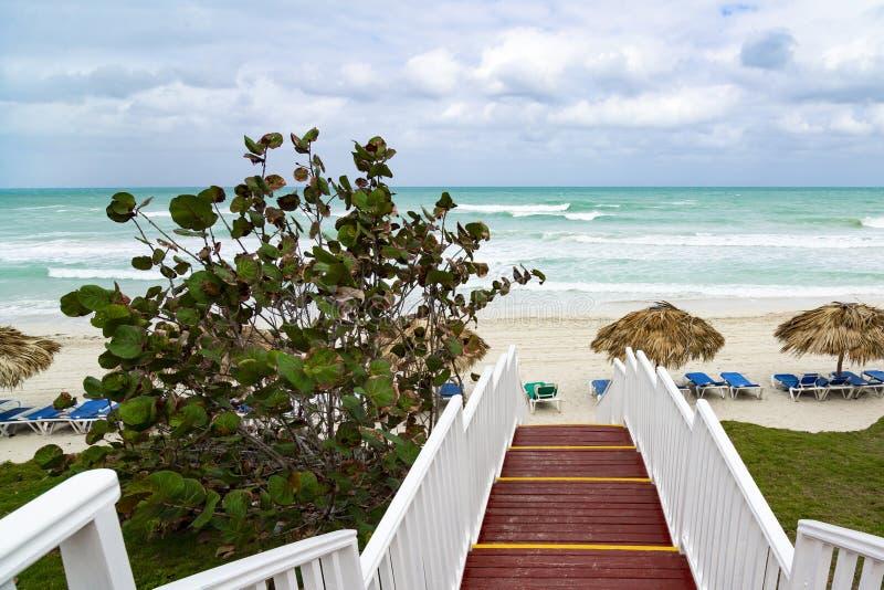 Piękna drewniana drabina ocean plaża Plaża z słomianymi parasolami i loungers Chmurny niebo i błękitne wody zdjęcie stock