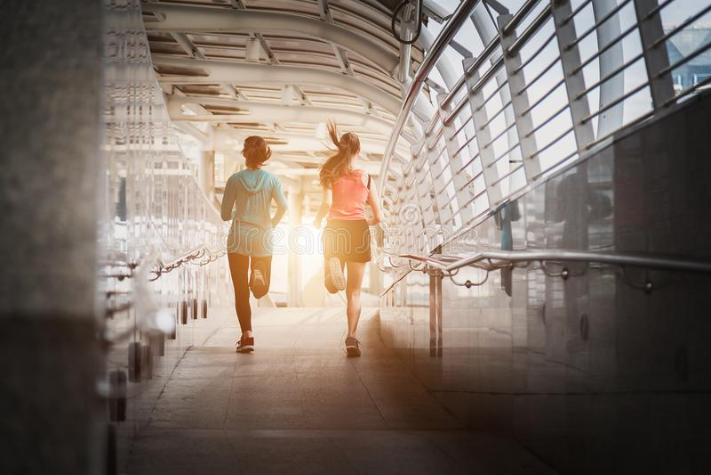 Piękna dwa kobieta biega nad mostem podczas zmierzchu zdjęcia stock