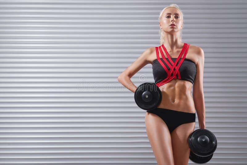 Piękna dysponowana młoda sportsmenka ćwiczy z dumbbells obraz stock