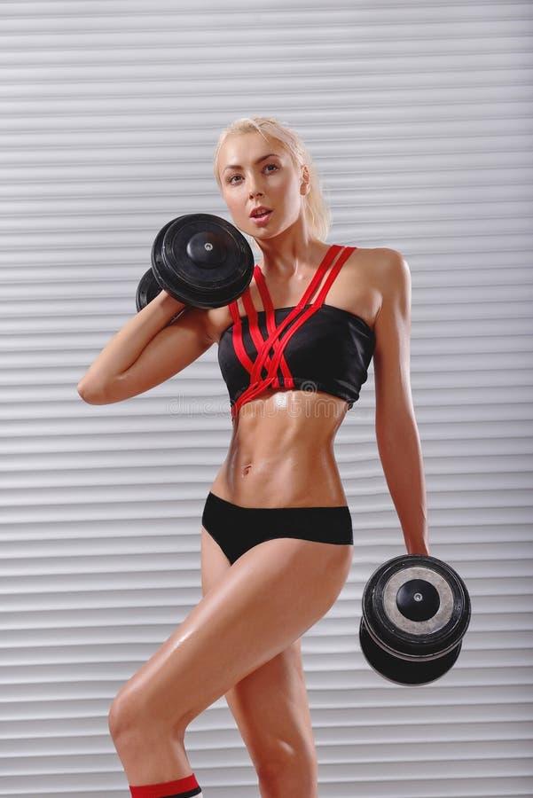 Piękna dysponowana młoda sportsmenka ćwiczy z dumbbells zdjęcie stock