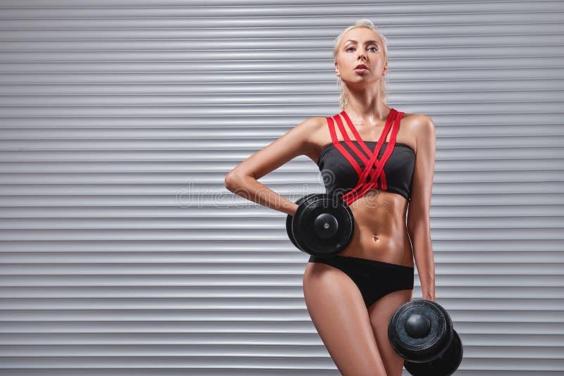 Piękna dysponowana młoda sportsmenka ćwiczy z dumbbells fotografia stock