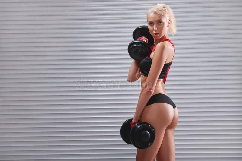 Piękna dysponowana młoda sportsmenka ćwiczy z dumbbells obrazy royalty free